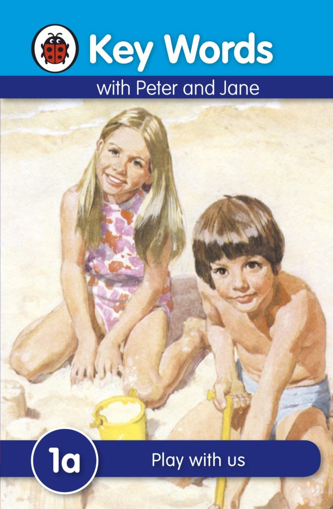 """a more modern version of a peter and jane book cover, updated in the 70s or 80s. It shows a blonde Haired girl in a pink bathing suit and a dark haired boy in a blue bathing suit sitting on a sandy beach. They are staring at the reader and smiling (as always, Jane is smiling much more widely than Peter) and the title above them reads """"Play with Us"""""""