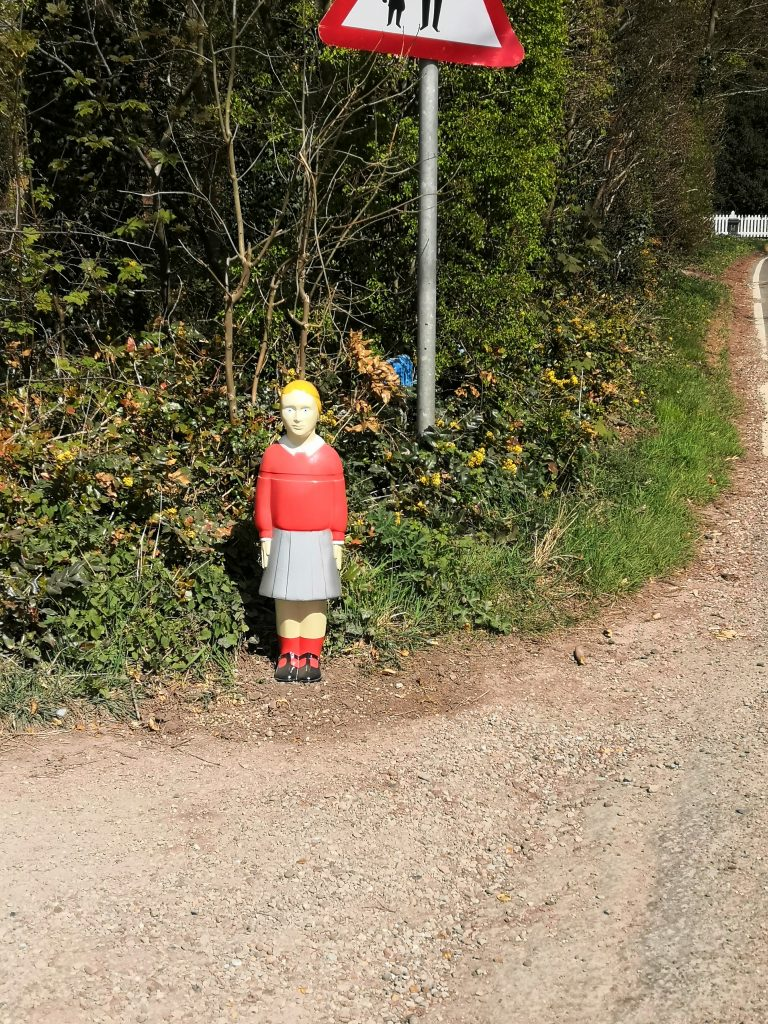 Image shows an unconvincing and creepy plastic statue of a school girl, next to a road traffic sign that warns of pedestrians in the road.  She stands around three feet high, very straight backed with her arms straight by her sides like a soldier standing to attention. She has unnaturally bright yellow hair, a painted on red school jumper, grey school skirt and red socks, with black buckle up shoes. Her eyes are piercingly bright blue.