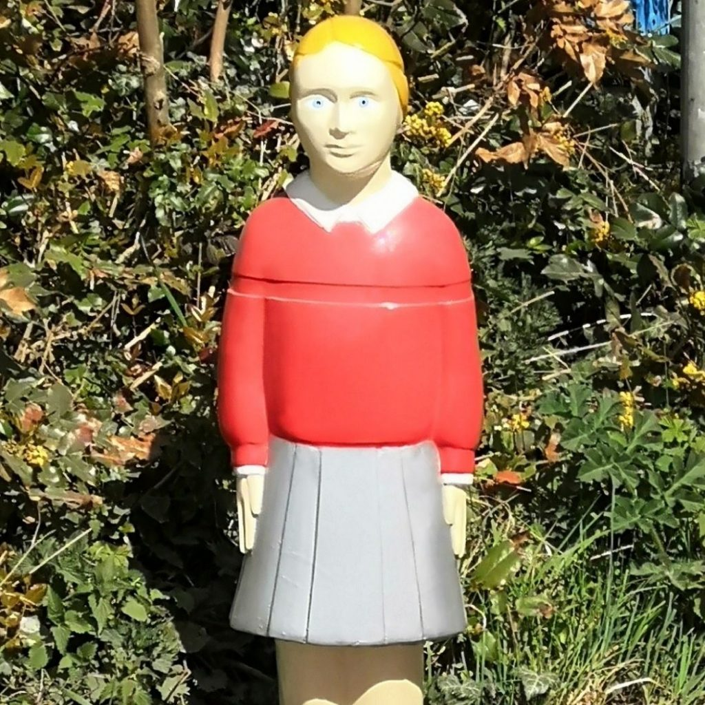 a more zoomed in image of the girl statue in the image above, so that she appears closer. you can no longer see her legs, but can see the waistband of her grey skirt, and her torso and face above.